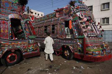 A boy walks past decorated buses parked along a street near the terminus in Karachi