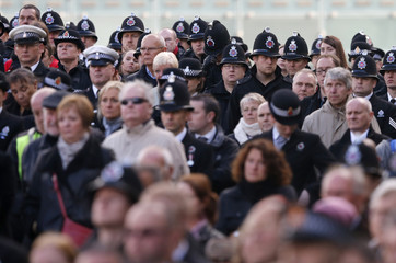 Police officers and members of the public watch as the coffin of Greater Manchester Police constable Nicola Hughes is carried into Manchester Cathedral for her funeral service in Mancheste