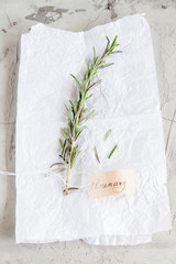 A branch of rosemary with a calligraphic inscription on a white and concrete background.