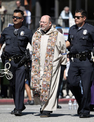 Father Chris Ponnet is arrested in an act of civil disobedience as people mark the 10th anniversary of the war in Afghanistan with a march and protest in Los Angeles