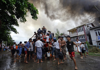 Ethnic Rakhine people get water from a firefighter truck to extinguish fire set to their houses during fighting between Buddhist Rakhine and Muslim Rohingya communities in Sittwe