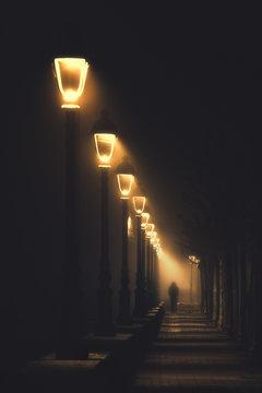 person walking on dark street illuminated with streetlamps
