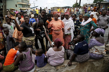 A video journalist interviews residents after a fire in Idimu neighbourhood in Nigeria's commercial capital Lagos