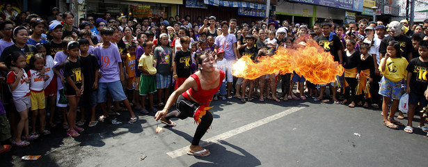 Residents watch a street performer blows fire into the air during a religious festival in Manila