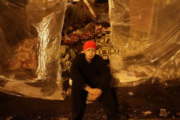 An opposition supporter sits outside his makeshift home early morning after Mubarak stood down in Tahrir Square