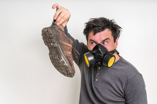 Man with gas mask is holding dirty stinky shoe