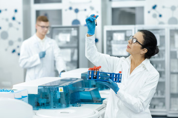 Senior woman professional chemist working with blood samples at the modern laboratory