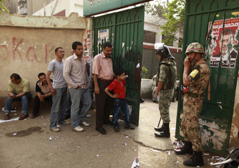 Soldiers stand guard as people wait outside a polling station in Cairo