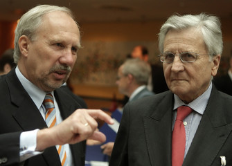 Austrian National Bank Governor Nowotny talks with European Central Bank (ECB) President Trichet before a conference hosted by Austrian National Bank in Vienna
