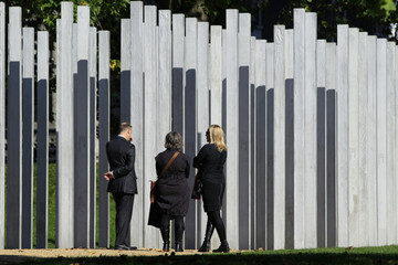 People stand in front of the memorial to the victims of the July 7 London bombings, in Hyde Park, in central London