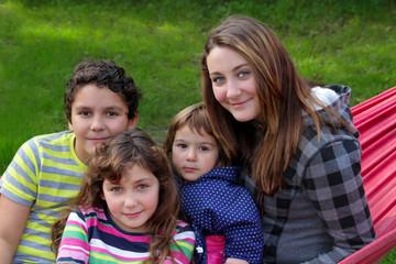 Vier lächelnde Geschwister sitzen in Hängematte im Garten