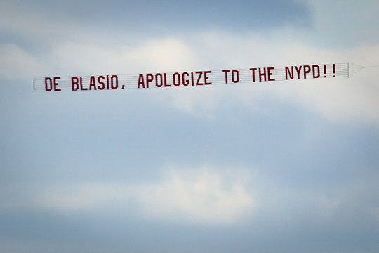 """Banner reading """"de Blasio, apologize to the NYPD"""" towed by an airplane flies over the Hudson River in New York"""