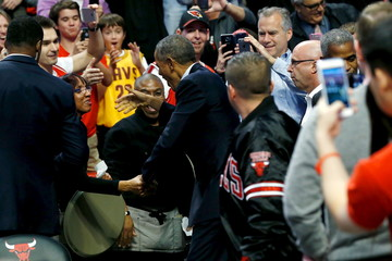 Obama greets fans as he attends an NBA opening night game between the Cleveland Cavaliers and the Chicago Bulls in Chicago