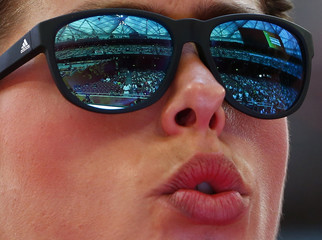 """Blanka Vlasic of Croatia competes in the women's high jump qualifying round with the """"Bird's Nest"""" stadium reflected in her sunglasses"""