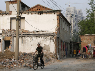 A woman riding a bicycle goes past a partially demolished house in a village as a building under construction is seen in the background, in Beijing