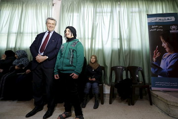 New United Nations High Commissioner for Refugees Filippo Grandi poses for a picture with a youth with a drawn mustache inside al-Iwaa centre in Damascus