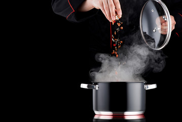 Photo sur Plexiglas Cuisine Modern chef in professional uniform adding spice to steaming pot