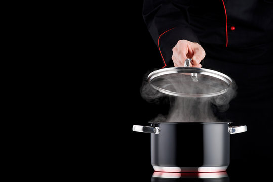 Steaming black pot on induction cooker, modern chef in professional uniform in background
