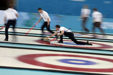Germany's fourth Felix Schulze delivers a stone during their men's curling round robin game against the U.S. at the 2014 Sochi Winter Olympics