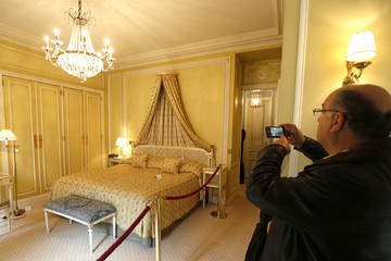 A visitor takes pictures of furniture displayed for auction in a bedroom at the Hotel de Crillon in Paris