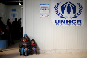 Syrian refugees wait to receive treatment at a health center at Al Zaatari camp