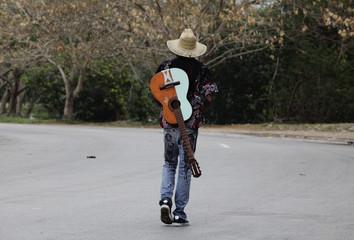 A man carries his guitar on a street in Havana