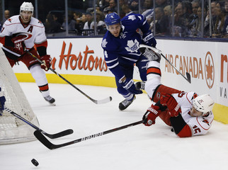 Hurricanes' Ruutu falls to the ice for a puck in front of Leafs' Franson during the first period of their NHL hockey game in Toronto
