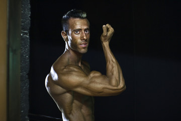 A contestant from National Amateur Bodybuilders Association (NABBA) Israel poses for a photo backstage during preparations for their annual national competition in Netanya
