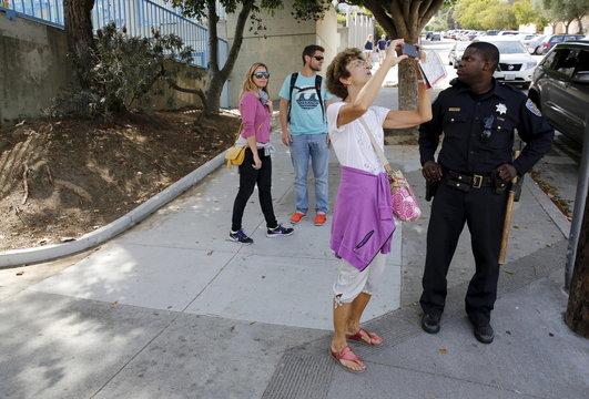 A woman snaps a photo near Lombard Street in San Francisco