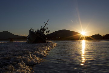 Sun sets near the rusty hulk of a ship that is stranded on the beach in Yuzhno-Kurilsk, the main settlement on the Southern Kuril island of Kunashir