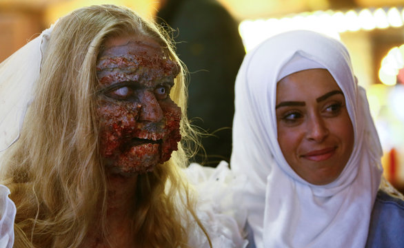 """A Muslim woman poses for a picture with a zombie bride during a so-called """"zombie walk""""  on Halloween Day in Essen"""