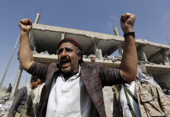 Houthi militant reacts in front the offices of the education ministry's workers union, destroyed by Saudi-led air strikes, in Yemen's northwestern city of Amran
