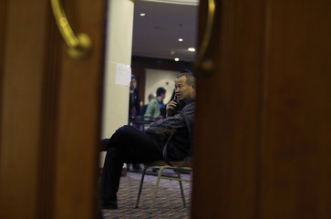A relative of a passenger of the missing Malaysia Airlines flight MH370 ispeaks on a mobile phone as he waits for updates from the airline, at a hotel in Beijing
