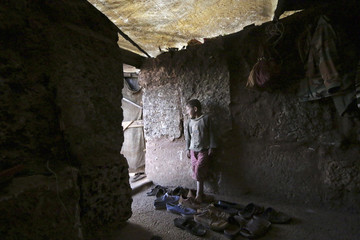 A child refugee from Kvromh village stands inside a makeshift house in the Serjilla archaeological site of Jabal al-Zawiya