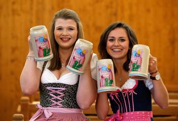 Models hold official Oktoberfest beer mugs during presentation in Munich