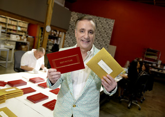 Creative director Marc Friedland, who designed the envelopes and announcement award cards bearing the names of the Oscar winners, holds up two blank envelopes in preparation for the 87th Academy Awards in Los Angeles