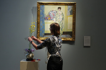 """Lisa Doucett, from the Spade and Trowel Garden Club of Andover, works on a floral arrangement related to Frederick Carl Frieseke's painting """"The Yellow Room"""" for Art  In Bloom at the Museum of Fine Arts, Boston"""
