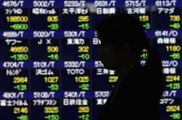 A pedestrian walks past stock quotation board displaying various stock prices outside brokerage in Tokyo