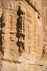 Close up of carving on stone Djinn block marking the entrance of a tomb in Petra Jordan, the ancient Nabataean city of Raqmu near Wadi Musa.