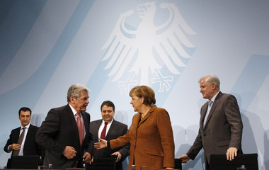 German Chancellor Angela Merkel and former East German rights activist Joachim Gauck leave with party leaders after a news conference at the Chancellery in Berlin
