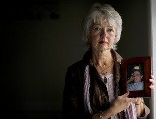 Terri Roberts, the mother of Amish school shooter Charles Roberts, holds a photograph of her son at New Covenant Community Church in Delta