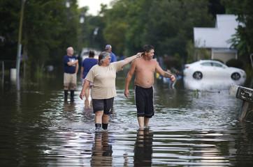 Residents survey flooding on Lee Street after heavy rains in Sorrento, Louisiana