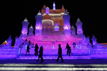 People visit ice sculptures illuminated by coloured lights on the opening day of the Harbin International Ice and Snow Festival in the northern city of Harbin