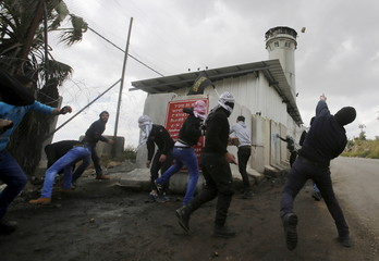 Palestinians throw stones at an Israeli outpost during clashes in Beit Omar village near the West Bank city of Hebron
