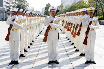 Honor guards twirl their rifles for Japanese Defense Minister Itsunori Onodera and U.S. Secretary of Defense Chuck Hagel at the Ministry of Defense in Tokyo