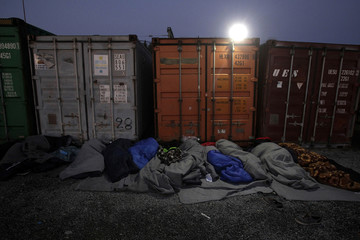 Refugees and migrants sleep next to containers as they wait to be allowed to cross the Greek-Macedonian border, near the city of Polikastro
