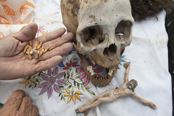 A Maya Indian man holds up teeth next to a skull of a dead relative in the village of Pomuch in Mexico's Yucatan peninsula