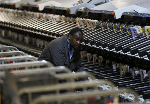 A postal worker helps run an intelligent sorting machine at Mount Pleasant sorting office in London