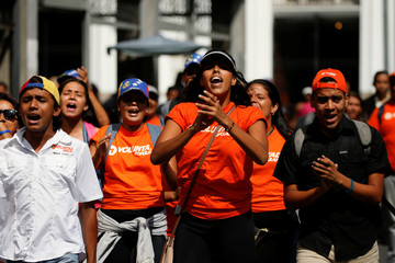Supporters of jailed Venezuelan opposition leader Leopoldo Lopez, shout slogans as they wait for his hearing at a courthouse in Caracas
