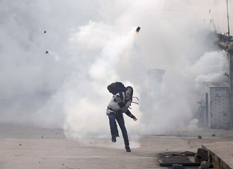 A Kashmiri demonstrator throws back a teargas canister fired by Indian police during a protest in Srinagar